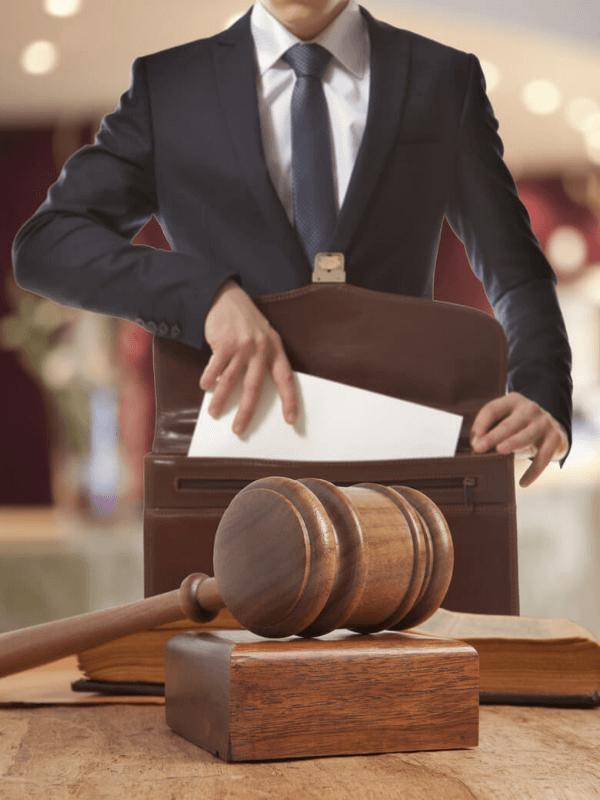 עורך דין מכניס מסמכים לתיק ופטיש על שולחן